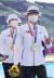 양궁 안산이 25일 일본 도쿄 유메노시마 공원 양궁장에서 열린 2020 도쿄올림픽 양궁 여자단체전 시상식에서 금메달을 목에 걸고 브이를 표시하고 있다.[뉴스1]