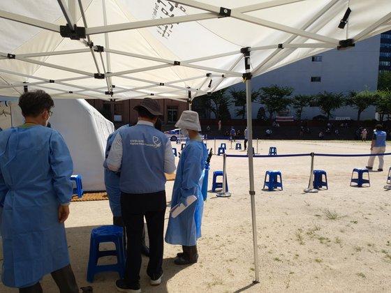 지난 7월 25일 오후 서울 명동성당 뒤편 라파엘 나눔 노숙자 무료 진료소 봉사자들이 진료 준비를 하는 동안 스탠드에서 노숙인들이 진료를 기다리고 있다. 강주안 기자