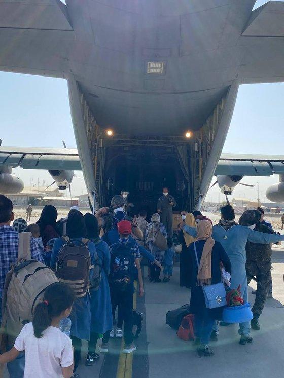한국정부 활동을 지원해 온 아프간 현지인 직원과 가족 391명이 25일(현지시간) 카불 공항에서 중간기착지 파키스탄 이슬라마바드 공항으로 이동하기 위해 공군 수송기에 탑승하고 있다. [사진 외교부]