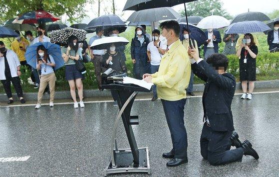 강성국 법무부 차관이 27일 오후 충북혁신도시 국가공무원인재개발원 정문 앞에서 아프가니스탄 특별기여자 초기 정착 지원을 발표하는 브리핑을 하는 동안 한 직원이 뒤쪽에 무릎을 꿇고 우산을 받쳐주고 있다. 뉴시스