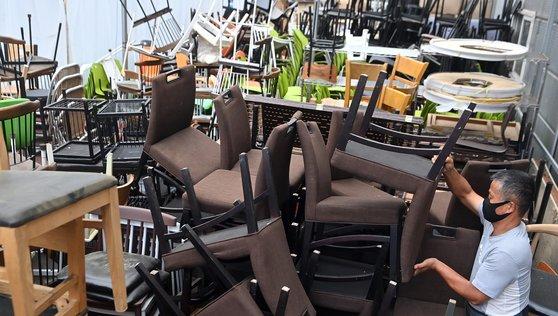 지난달 31일 오후 경기도 안성시 한 중고 주방용품 판매점에 폐업한 음식점에서 나온 의자가 수북이 쌓여있다. 고용노동부가 발표한 사업체 노동력 조사 결과에 따르면 코로나19 4차 대유행의 여파로 숙박·음식업 종사자가 7월에 6만4000명 감소한 것으로 나타났다. [뉴시스]