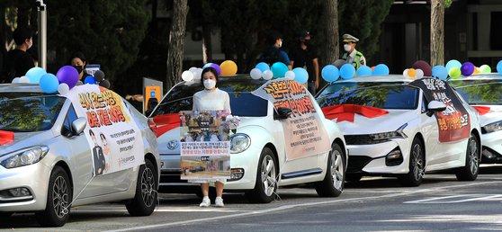예비부부 등으로 구성된 전국신혼부부연합회 회원이 15일 오전 서울 영등포구 여의도공원 인근 공영주차장에서 정부의 신종 코로나바이러스 감염증(코로나19) 방역지침에 반발하며 '웨딩카 주차시위'를 하고 있다. 뉴스1