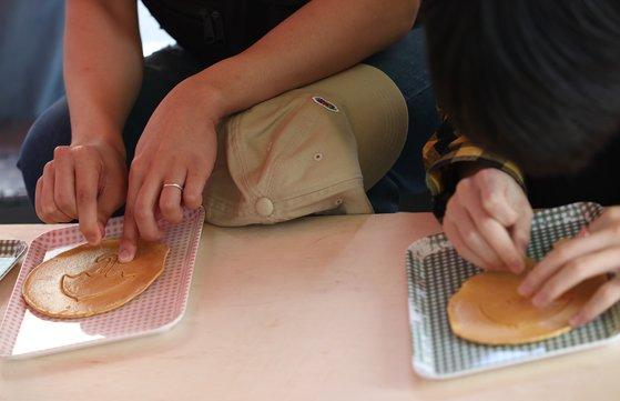 지난달 30일 오후 서울 종로구 대학로의 한 뽑기 가게에서 시민들이 뽑기를 즐기고 있다. [연합뉴스]